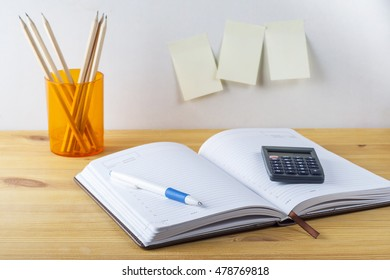Notepad with pen container with pencils, calculator are on a wooden table. White background. On the wall near the table glued paper for notes.