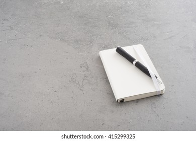 Notepad and pen lying on empty office table. White notebook and black pen. Concept of business meeting, taking notes or a clean desk.