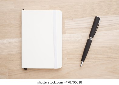 Notepad and pen lying on office desk in close up. Concept of business meeting, taking notes or education.
