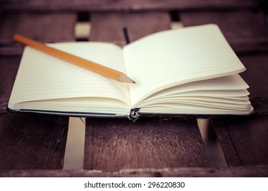 notepad with pen on brown wood table background
