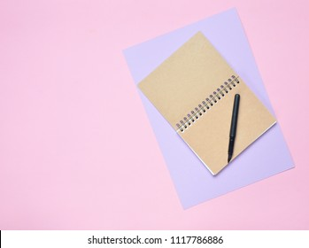 Notepad with pen on colored paper background. Girly diary. Top view.