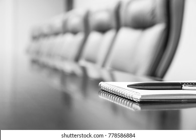 notepad and pen on table in empty conference room, black and white