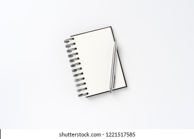 Notepad with pen on white background