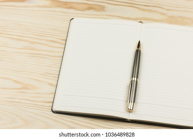 Notepad with pen  on wooden background