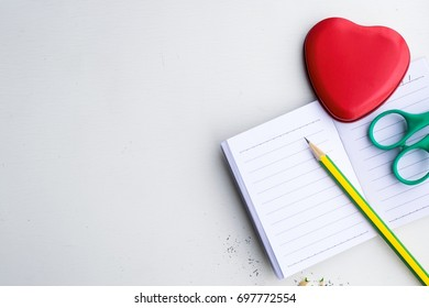 Notepad with pencil and heart shaped on wood board background. using wallpaper or background for education, business photo. Take note of the product for book with paper and concept or copy space.