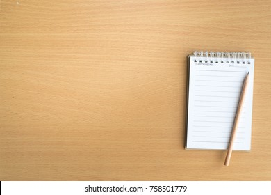 Notepad with pencil on wood board background.using wallpaper for education, business photo.Take note of the product for book with paper and object, concept or copy space.