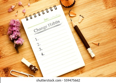 notepad with  pencil  on wooden table for change habits  list concept , overhead shot or Top view