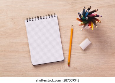 Notepad, pencil, rubber and colored penils on wooden office desk. - Shutterstock ID 287309342
