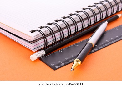 Notepad, pencil, ruler and pen on orange background