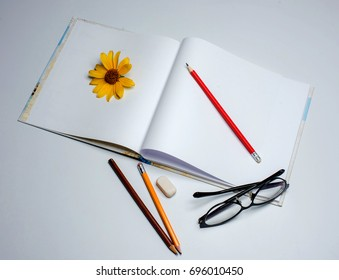 Notepad, pencils glasses, yellow flower on a white background