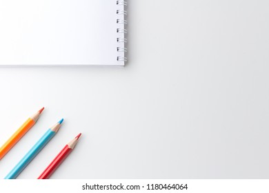 Notepad with pencils on white table.