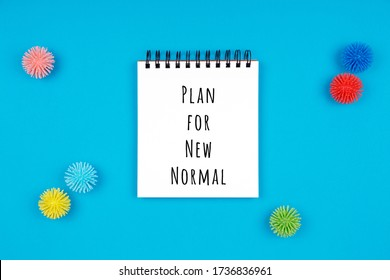 Notepad with plastic balls as viruses on blue with Plan for New Normal wording. Coronavirus pandemic reduction, moving to new normal, economy reopening concept. Isolated white paper of the notepad