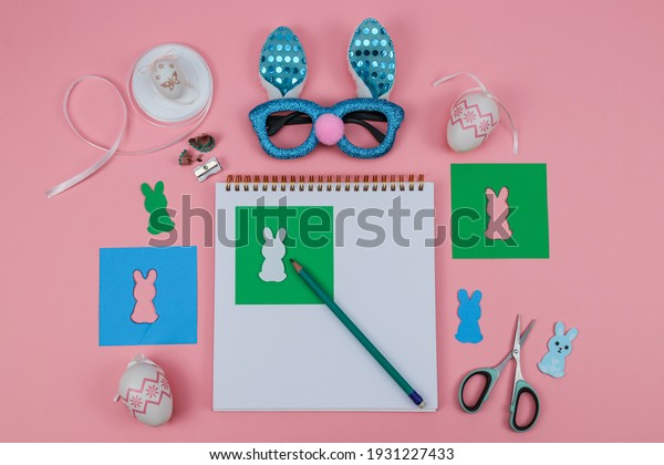 Notepad, scissors, glasses, pencil, colored paper and a rabbit on a pink background, top view close-up.