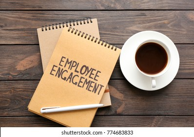 Notepad with text EMPLOYEE ENGAGEMENT and coffee on table