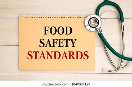 Notepad with text Food Safety Standards on the office desk and stethoscope