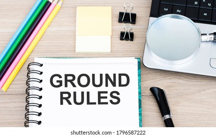Notepad with text GROUND RULES on a white background, near office supplies. Business concept.