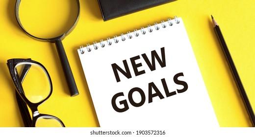 Notepad mit dem Text NEUE ZIELE auf gelbem Hintergrund mit Brille, Lupe und Bleistift. Geschäftskonzept.