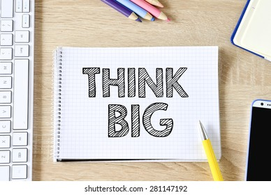 Notepad with think big , keyboard,mobile phone and pencils on wooden background