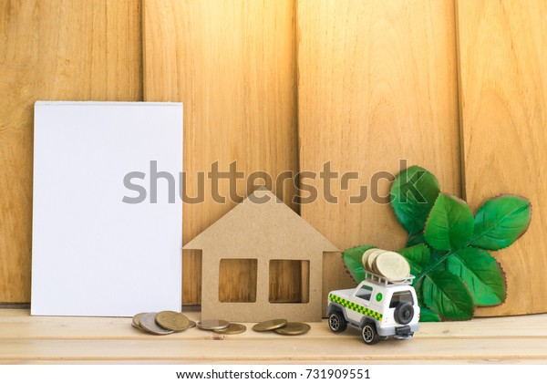notepad with toy car and home paper on wood background. Using wallpaper or background for the trip and success image