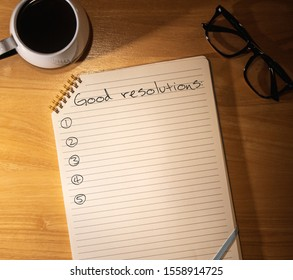 """notepad in warm and soft light with coffee and glasses. text """"good resolutions"""" for the new year"""