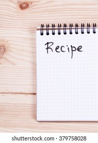 Notepad with the word recipe on a wooden board