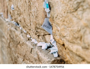 Notes on the wailing (Western) wall in Jerusalem Israel. Peace written in one of the notes