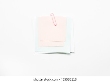 Notes paper and pink  paper clip isolate on white background.