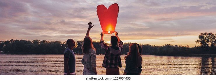 Nothing is better than old friends. Full length of young people in casual wear preparing sky lantern while standing on the pier