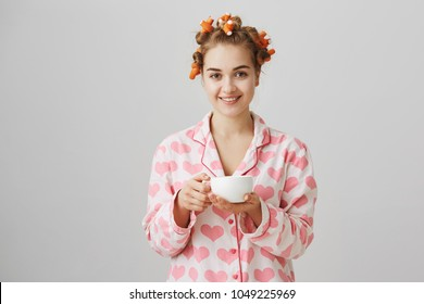 Nothing can be better than coffee in morning. Portrait of attractive friendly woman at home wearing hair curlers and pyjamas, offering cup of tea or drinking it while making beauty procedures