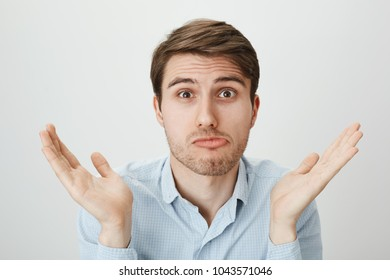 Nothing can be done. Portrait of confused attractive mature man with bristle shrugging and raising palms in questioned gesture, puckering lips, trying to hide his blame and pretend clueless