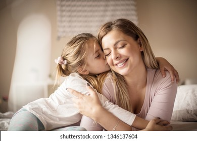 Nothing is greater than love for the mother. Mother daughter on bed.