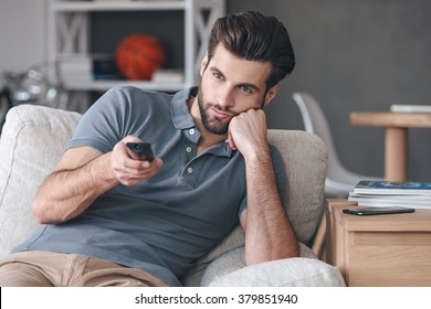 Nothing interesting to watch. Handsome young man holding remote control and looking bored while watching TV on the couch at home