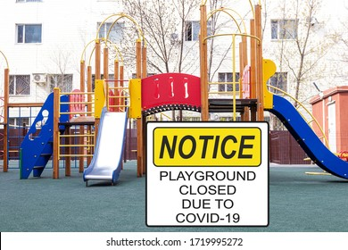 ''Notice. Playground closed due to COVID-19'' information sign against a closed playground
