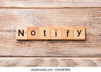 NOTIFY word written on wood block. NOTIFY text on wooden table for your desing, concept.