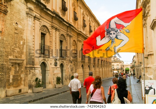 Noto, Italy - 21 July 2008: People walking on an alley of Noto on the island of Sicily, Italy