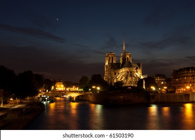 Notre Dame cathedral illuminated in Paris, France, just before dark, with golden lights reflected in the seine.