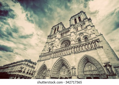 Notre Dame Cathedral in Paris, France. Artistic vintage mood. Main facade view.