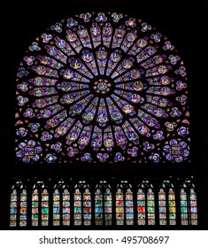Notre Dame Cathedral, Paris, France - August 22, 2010: The north rose window of the Paris Notre-Dame Cathedral, an example of Rayonnant architecture, and the row of figures in stained glass below.