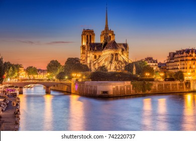 Notre Dame cathedral in Paris, France, at night against sunset sky. Scenic nighttime skyline.