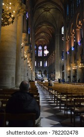 NOTRE DAME CATHEDRAL, PARIS/FRANCE - DECEMBER 2017: Interior view of NOTRE DAME CATHEDRAL with people praying, Paris/France.