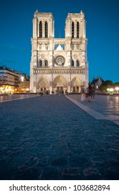 Notre Dame de Paris cathedral at night. Deep blue sky in background, copy space in foreground. Paris, France, Europe.