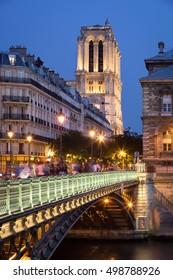 Notre Dame de Paris Cathedral and Pont Arcole illuminated in early evening with the Seine River. Ile de la Cite, Paris, France