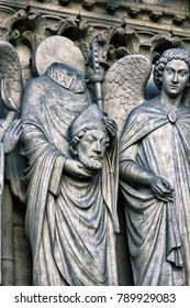 Notre Dame de Paris Cathedral Gothic style. Cephalophor. Architectural details. Saint Dionysius decapitated (nimbus remained on headless torso) and warmhearted angel. Severed head