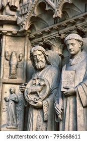 Notre Dame de Paris Cathedral. Architectural details. Catholic saints statues. Sheep as symbol of caring for devotees and narrow-toed crayfish (resident of French rivers) as warning against apostasy