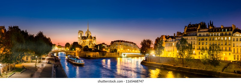 Notre Dame de Paris and Cite island at night captured from the bank of Seine river at sunset, beautiful panorama