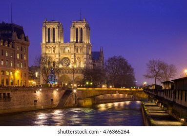 Notre Dame de Paris and Cite island at night captured from the opposite bank of Seine river