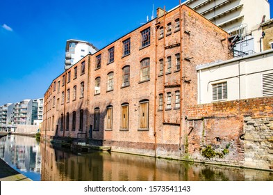 Nottingham city centre canal and building s with blue sky and refections in the water.
