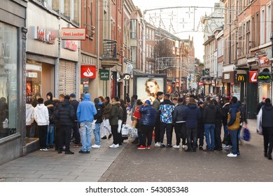 NOTTINGHAM, ENGLAND - DECEMBER 26: Boxing Day sale shoppers queue outside Footlocker sports store on Clumber Street. In Nottingham, England. On 26th December 2016.