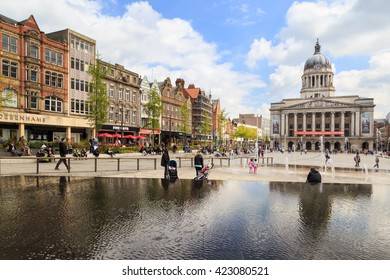 NOTTINGHAM, ENGLAND - MAY 17: Various people sitting, walking, visiting in the main Market Square,  Nottingham Council House building behind. In Nottingham, England. On 17th May 2016.