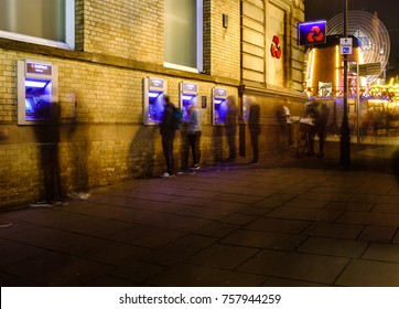 NOTTINGHAM, ENGLAND - NOVEMBER 18: Creatively blurred people withdrawing cash from Natwest Bank, Nottingham, at night. On Exchange Walk, Nottingham, England. On 18th November 2017.